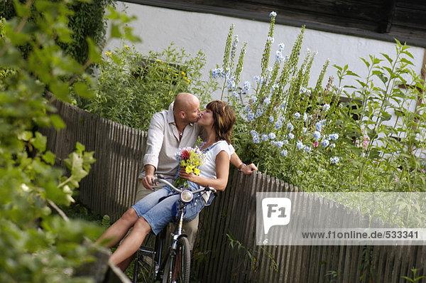 Paar auf dem Fahrrad sitzend  küssend