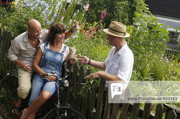 Paar sitzt auf dem Fahrrad und redet mit dem Nachbarn.