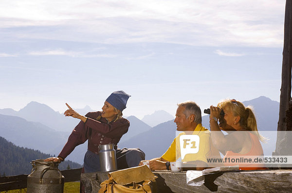 Couple at mountain hut  peasant woman pointing