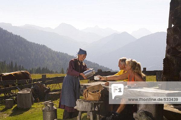 Paar macht Pause auf der Almhütte Bäuerin  die sie bedient