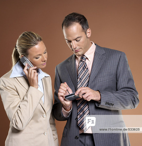 Geschäftsmann und Frau mit Handy und Palmtop