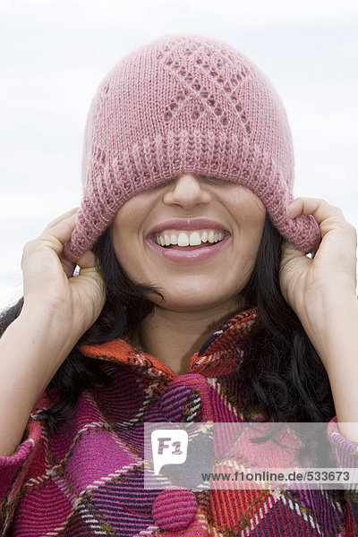 Young woman eyes covered by cap  smiling  close-up