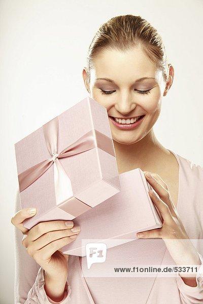 Junge Frau öffnet Geschenkbox  lächelnd  Nahaufnahme