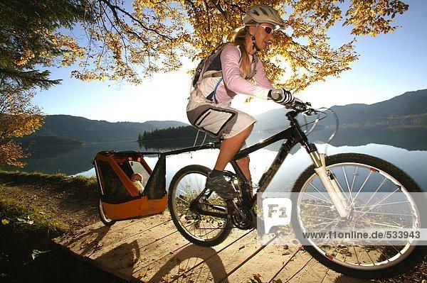 Frau Radfahren am See mit Kind im Anhänger