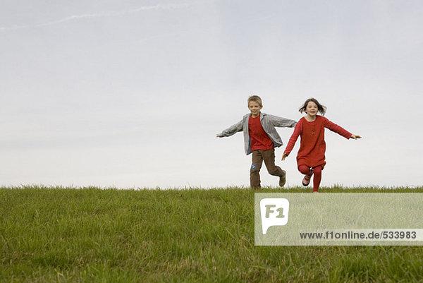 Junge (10-12) und Mädchen (7-9) rennen in Wiesenarmen ausgestreckt