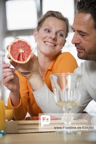 Reife Paare essen Grapefruit in der Küche  Frau lächelt