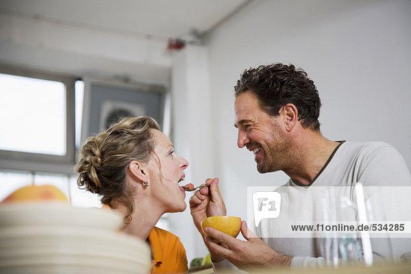 Reifer Mann füttert Grapefruit an Frau in der Küche  lächelnd  Blickwinkel niedrig