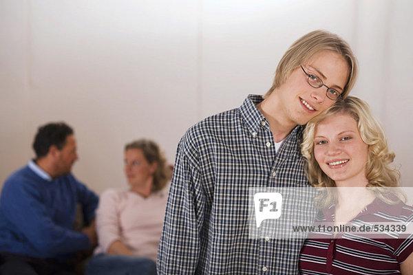 Teenager-Paar  Eltern im Hintergrund sitzend
