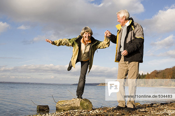 Senior couple hand in hand  woman standing on tree trunk
