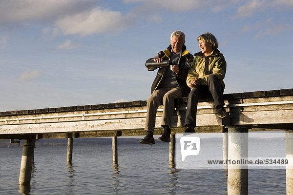 Seniorenpaar am Steg sitzend