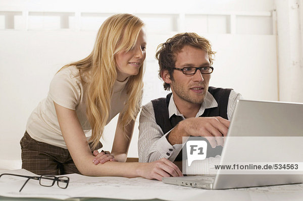 Young man and woman using laptop  smiling