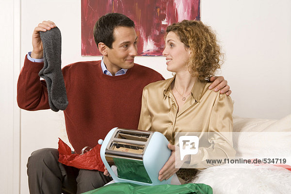 Couple sitting on sofa  holding toaster and socks