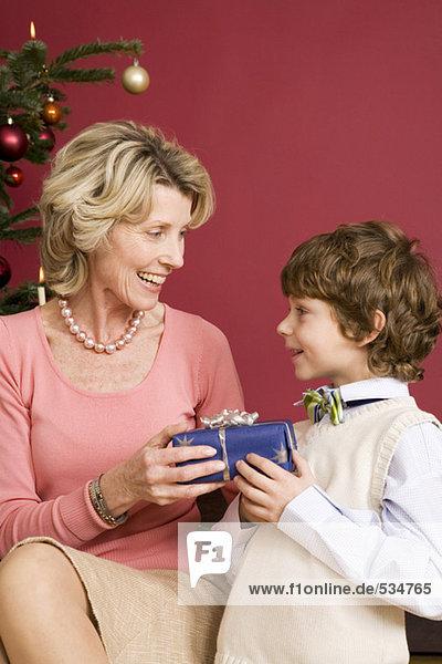 Kleiner Junge macht Großmutter ein Weihnachtsgeschenk.