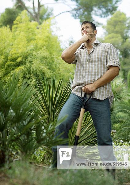 Man doing yard work  holding shovel  looking up