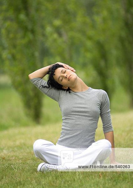 Junge Frau sitzend auf Gras  Hals stretching