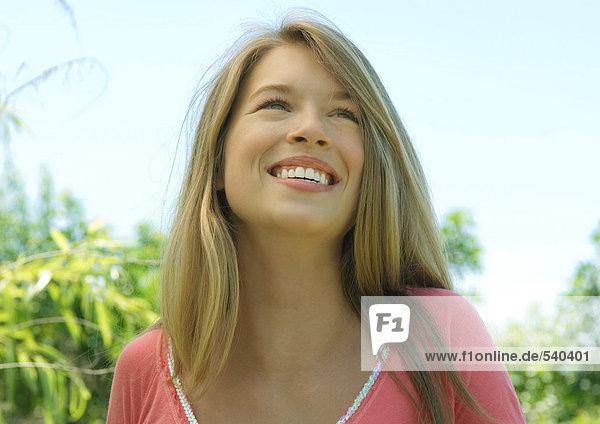 Junge Frau im Freien  lächelnd und Nachschlagen