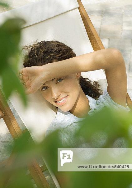 Frau sitzt im Liegestuhl  Shading Augen  erhöhte Ansicht Frau sitzt im Liegestuhl, Shading Augen, erhöhte Ansicht