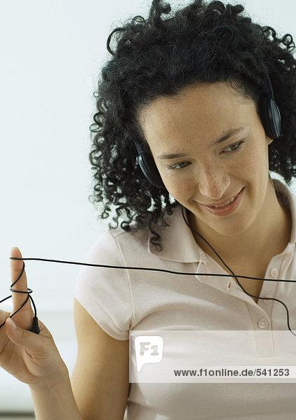 Frau hören Kopfhörer  Verpackung Schnur um finger