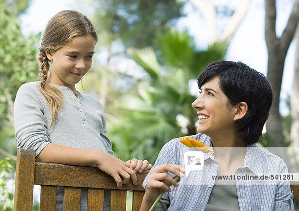 Frau hält Schnittblume  Blick auf Tochter
