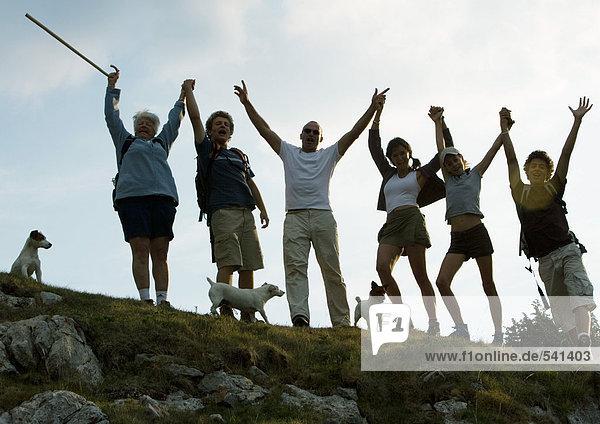 Wanderer stehen nebeneinander  Arme in die Luft