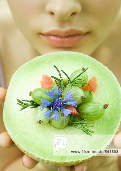Halten Sie die up Honeydew Melon gekrönt mit Beeren  Blumen und Rosmarin Zweige  Nahaufnahme Frau