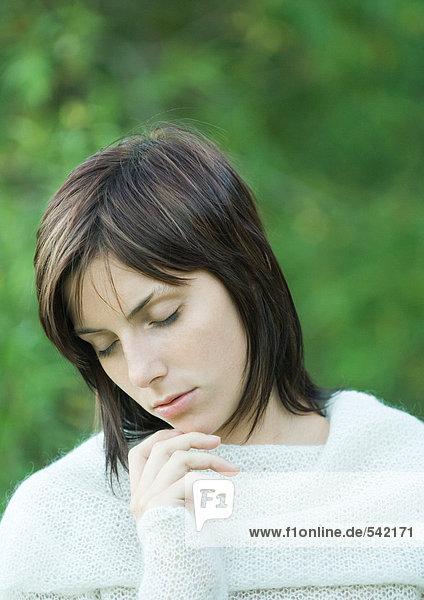 Frau mit Hand unter Kinn  Kopf und Schultern  Augen geschlossen