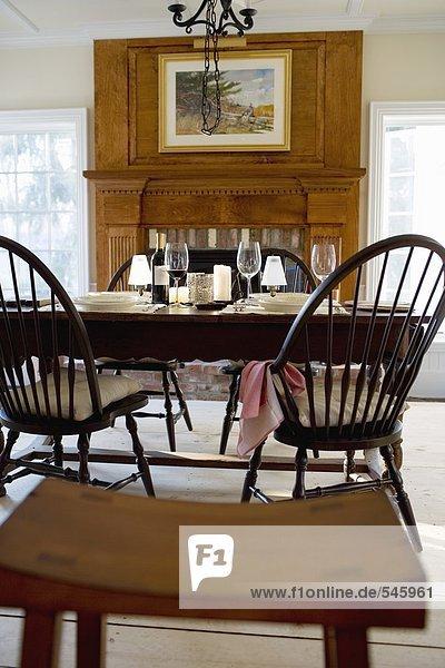 Gedeckter Tisch mit Rotwein vor einem Kamin