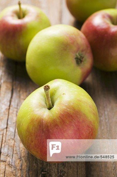 Mehrere frische Äpfel auf Holzuntergrund