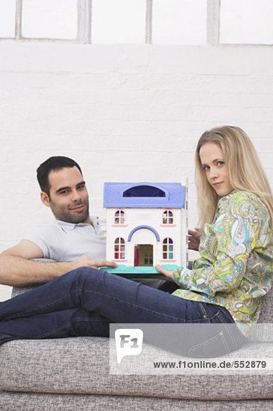 sitzend Zusammenhalt Wohnhaus Modell halten Sessel jung Miniatur