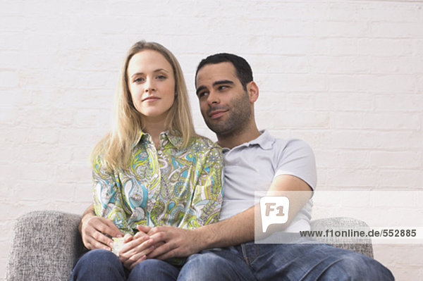 young couple sitting on armchair man tenderly embracing woman