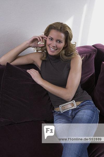 Portrait einer jungen Frau entspannenden auf sofa