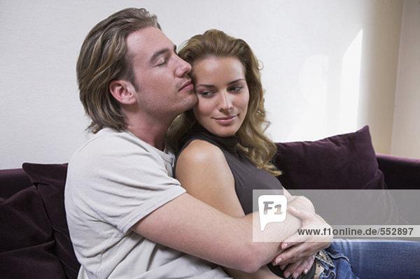 junges paar sitzen auf couch Mann zärtlich umarmung weiblich zusammen