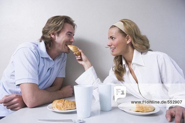 junges paar mit Frühstück Frau Mann Croissant Fütterung
