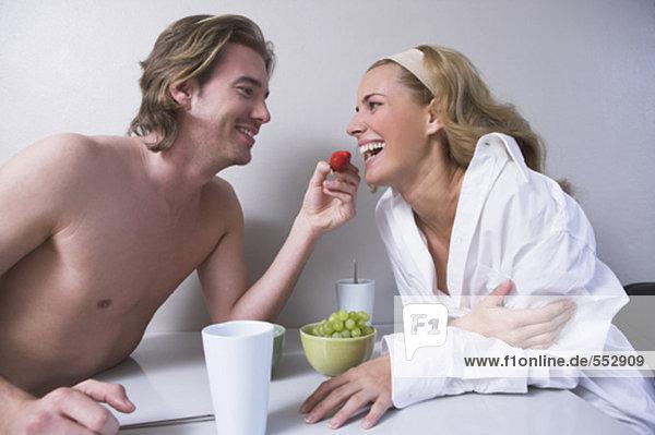 junges paar am Tisch zusammensitzen Mann Erdbeere Ernährung Frau