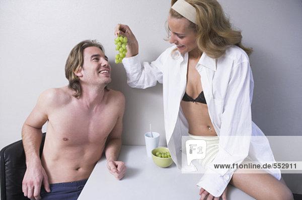 junges paar sitzen am Tisch weiblich Fütterung Mann weintraube