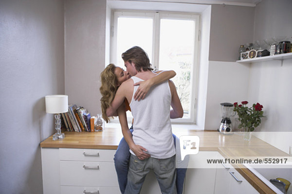 young couple passionately kissing in kitchen