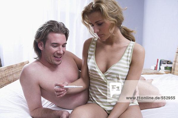 junges paar sitzen auf dem Bett zusammen überrascht vom Ergebnis der Schwangerschaftstest