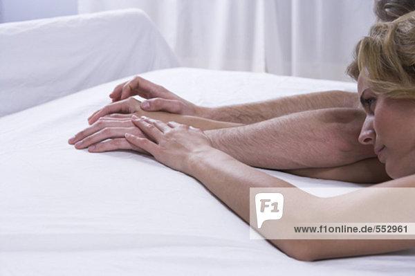 junges paar hält hände auf Bett