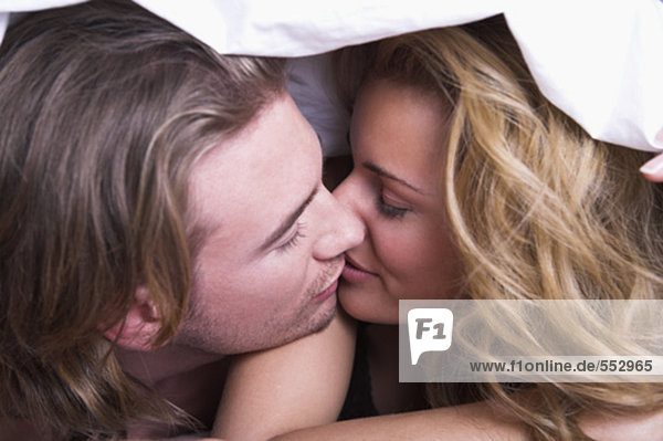 Porträt jungen Paares Küssen unter Bettdecke