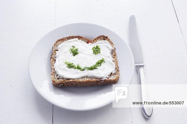Sandwich mit Frischkäse und Gesicht gebildet aus Schnittlauch Sandwich mit Frischkäse und Gesicht gebildet aus Schnittlauch