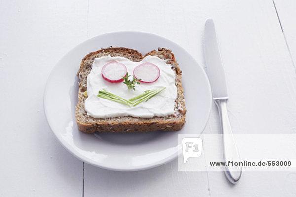 Sandwich mit Frischkäse und Gesicht gebildet aus Schnittlauch und Radieschen
