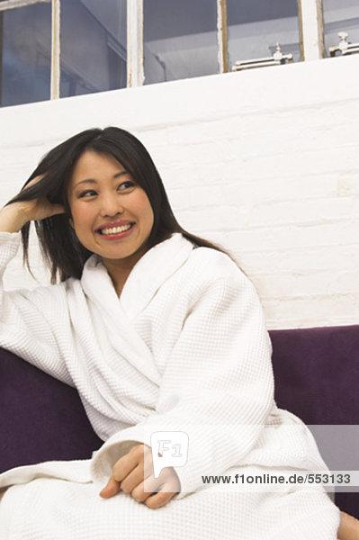 Portrait lächelnd junge japanische Frau sitzt auf Sessel