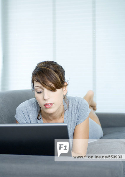 Junge Frau auf der Couch liegend  mit Laptop