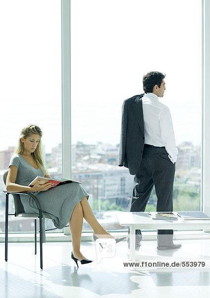 Wartezimmer  Frau sitzt im Lesemagazin  während der Mann aus dem Fenster schaut.
