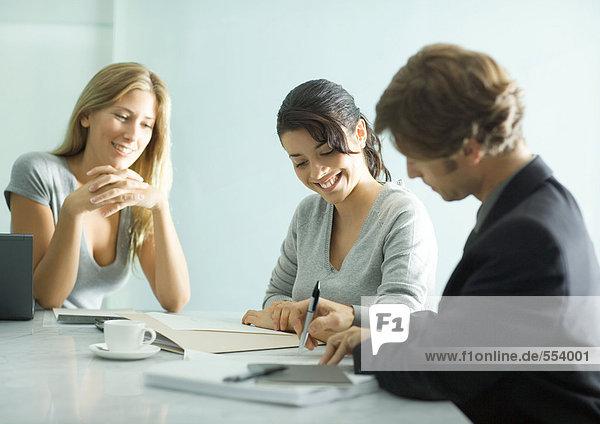 Erwachsener Mann am Tisch sitzend mit Teenagermädchen und junger Berufstätiger  Unterschriftsdokument