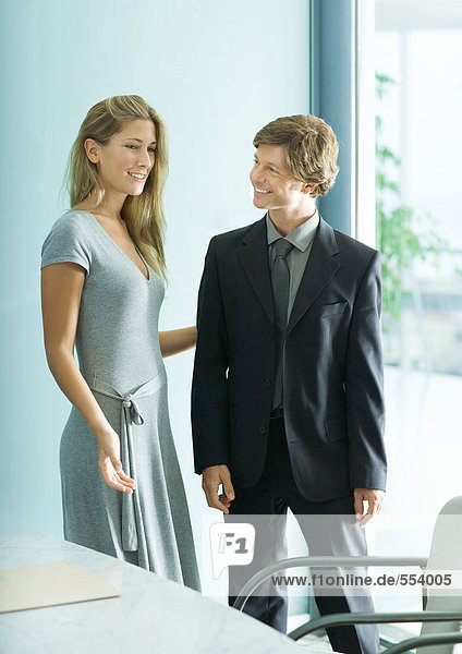 Young female professional showing mature businessman to chair