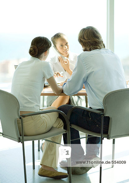 Young couple sitting across table from young female professional using phone