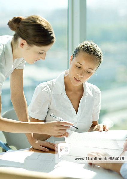 Two women discussing document together