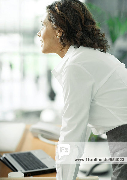 Mature female professional leaning against desk  looking away