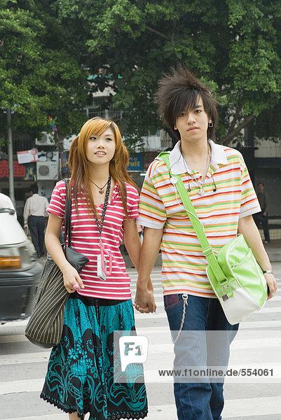 Junges Paar  das die Straße überquert  Händchen haltend  dreiviertel Länge